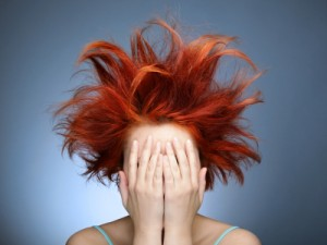 Redhead with messy hair covering her face with hands